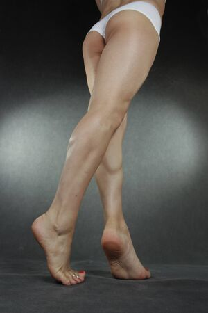 waxed: Woman legs and feet wearing underwear over grey background