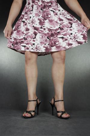 black heels: Woman legs wearing black heels and dress over grey