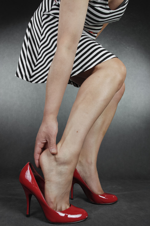 waxed legs: Woman legs and feet wearing  dress putting on  shoes over grey background