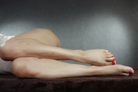 waxed legs: Woman legs and feet wearing underwear over grey background