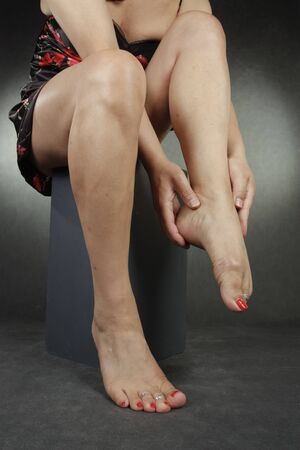 waxed legs: Woman lwgs and feet sitting over grey background