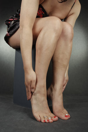 Woman lwgs and feet sitting over grey background