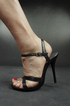 tacones negros: Woman legs wearing black heels over grey Foto de archivo