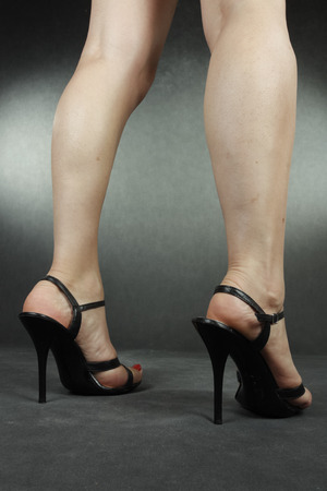waxed legs: Woman legs wearing black heels over grey Stock Photo