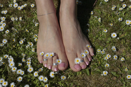 Female feet relaxing on grass lawn with flowers