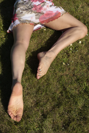 female legs: Female legs relaxing on grass lawn with flowers Stock Photo