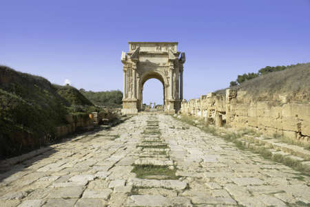 severus: Leptis Magna, Libya  Roman Cobbled road leading to the Arch of Septimius Severus  Stock Photo