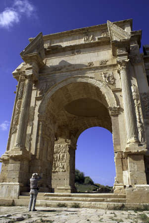 architrave: Wide angle View of the arch of Septimus Severus at Leptis Magna with man taking picture