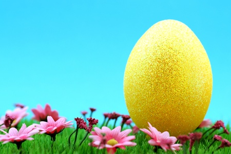 giant easter egg: Giant gold-yellow Easter egg on a nice green meadow with pink flowers and fresh blue sky background