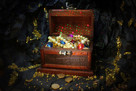 perls: enchanted treasure box with perls, gems, diamonds and gold coins in mystic gold mine cave with gold nuggets Stock Photo