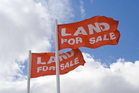 Two Land for Sale flags flying high against a lightly clouded blue sky