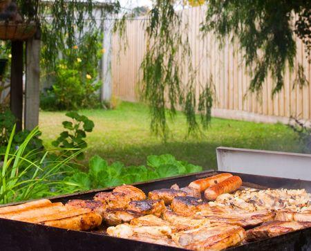 Backyard barbecue con salsicce, ossa, bistecca e cipolle