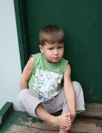 doorstep: Young boy sitting on the doorstep with bare feet and worried look
