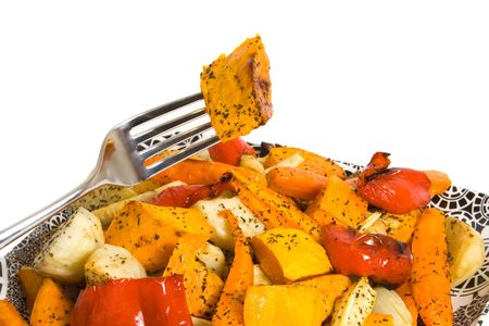 accompaniment: Fork lifting roast pumpkin from a platter of roasted vegetables over white background. Stock Photo