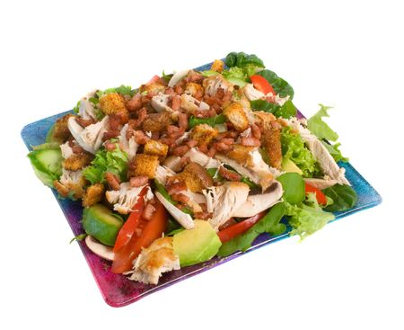 Warm chicken salad on serving plate isolated over white background.