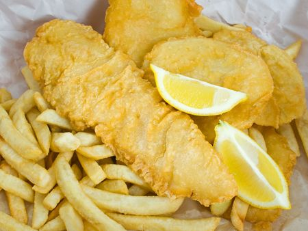 Traditional deep fried fish and chips with lemon in paper wrapping