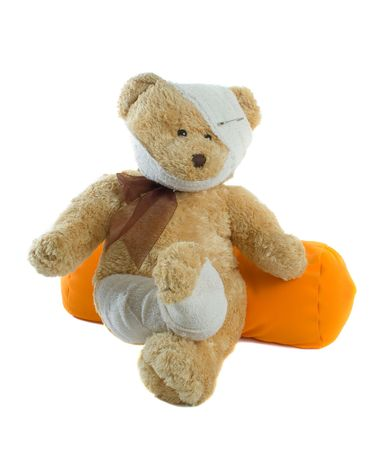 Injured teddy bear with bandages on head and leg isolated over white background photo