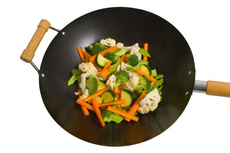 Fresh sliced vegetables in wok over white background.