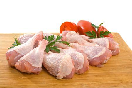Fresco crudo ali di pollo su tagliere con pomodori roma
