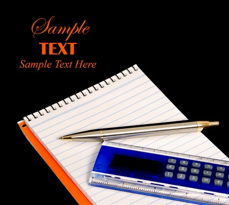 Pad, pen and calculator ruler over black background with copy space for text photo
