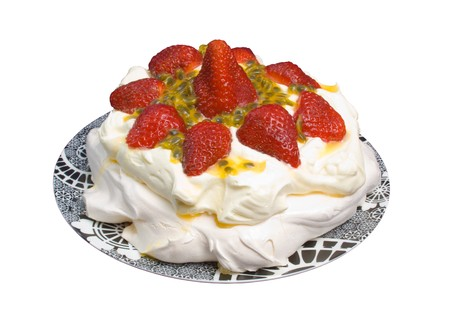 Pavlova with strawberries and passionfruit over white background.