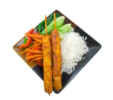 indonesian food: Meal of Chicken Satay Sticks, rice, and stir fry vegetables.