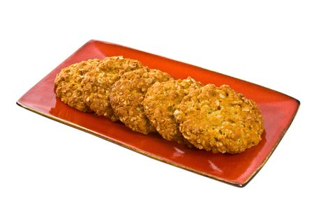 Traditional Australian Anzac Biscuits on red plate isolated over white background. Stock Photo