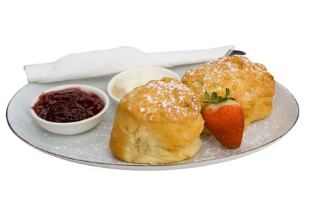 Freshly baked scones, jam and cream on serving plate.