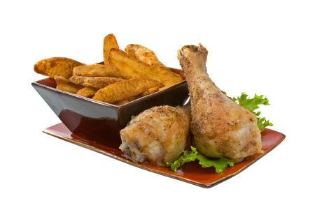 Chicken legs and potato wedges on serving platter isolated over white background.
