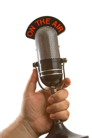 newscast: Retro Microphone held in hand over white background. Stock Photo