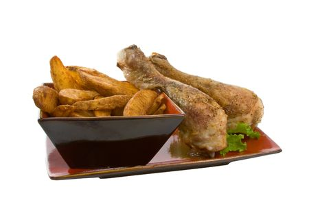 Chicken legs and potato wedges on serving platter isolated over white background. Stock Photo - 4760526