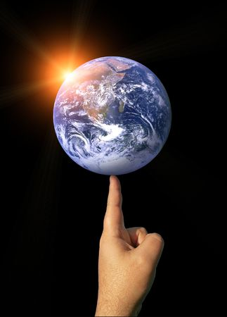 A finger balancing the whole earth with the concepts of environmental awareness and balancing the global economy Stock Photo