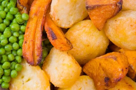 Crisp roast vegetables including potatoes, pumpkin and carrot with peas. Stock Photo - 5286972
