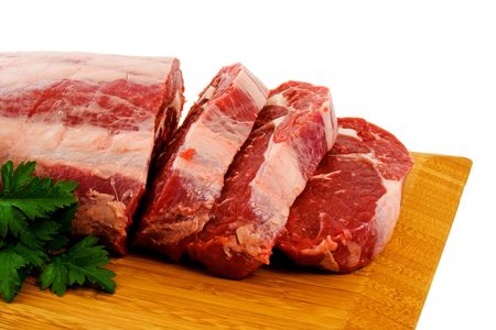 Piece of Raw Scotch Fillet being cut into steaks. Stock Photo