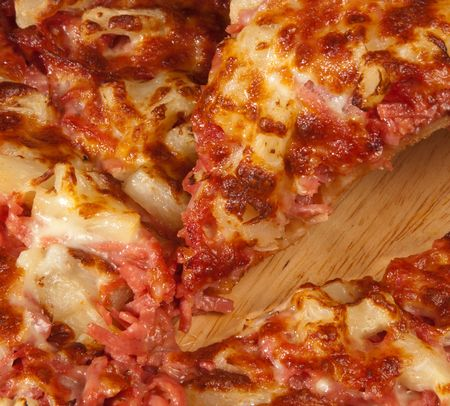 Freshly baked ham and pineapple pizza cut into slices photo