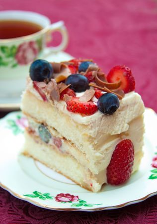 Delicious slice of berry sponge cake with strawberries, blueberries and milk chocolate shavings. Stock Photo
