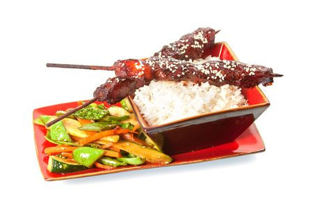 Honey Soy Chicken Sticks with stir fry vegetables and rice isolated over white background