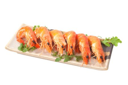 Delicious fresh prawns served on a ceramic platter over white background. Stock Photo