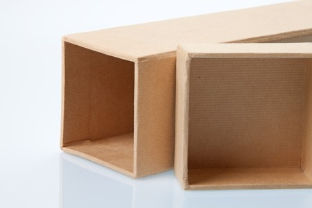 Cardboard box laying on its side with seperate lid with reflection Stock Photo