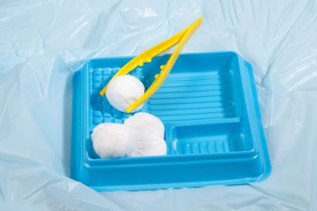 Sterile wound care kit with tweezers and cotton balls.