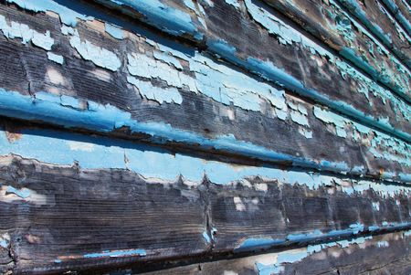 Timber weatherboards with flaking blue paint