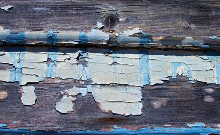 Weathered timber wall with flaking paint showing wood grain underneath Stock Photo