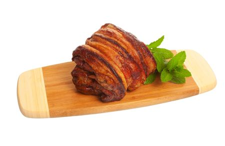 Roasted rolled shoulder of lamb on chopping board with mint, isolated over white background. Stock Photo