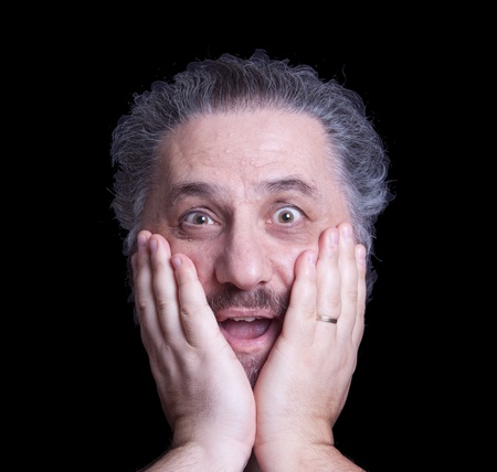Surprised mature man holds his disembodied head between his hands over a black background. Stock Photo
