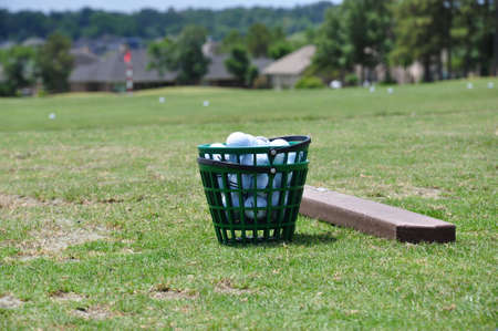 Bucket of golfballs on the driving range Stock Photo