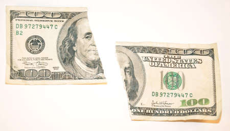 a one hundred dollar bill torn in half on a white background