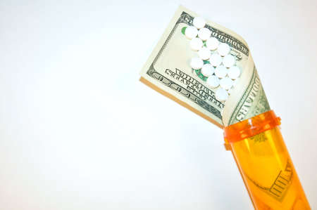 A perscription bottle with a $100 dollar bill spilling out with white pills