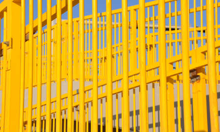 Pattern of bright yellow vertical stair railing against a blue sky