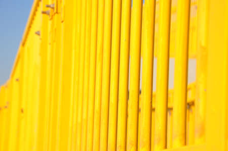 close up of the pattern of vertical bright yellow stair railings