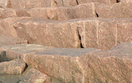 closeup of a granite seawall in the sunlight